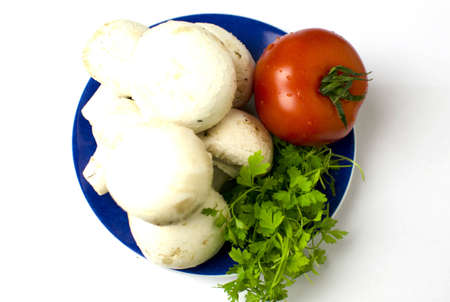 A bunch of mushrooms, a tomato and parley are on placed on a blue plate. Shallow depth of the field.  Stock Photo