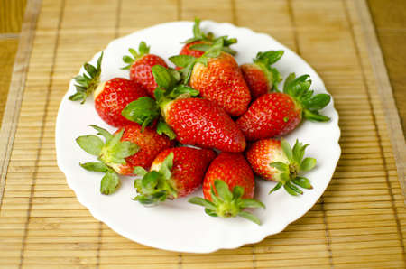 Fresh strawberries are placed on a plate. Shallow depth of the field.