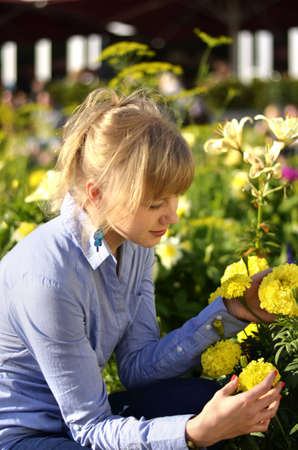 A beautiful young girl is looking at the flowers and is enjoying a good weather in a park