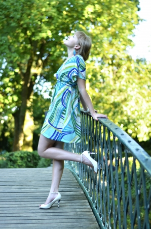A beautiful young gril is standing on the bridge and is dreaming about something  Stock Photo