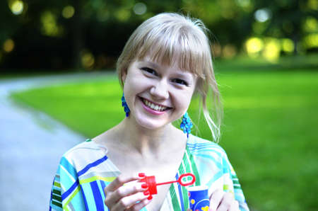 A beautiful young girl is smiling as it makes too much fun making soap bubbles
