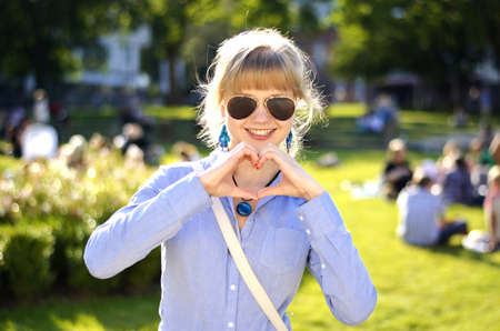 I beautiful young girl is showing a heart with her hands.