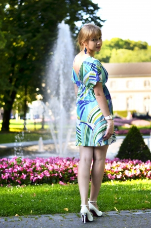 A beautiful young girl is posing in front of the fountain in the park turning her back to the camera and looking right into it. photo