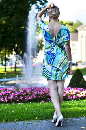 A beautiful young girl is posing in front of the fountain in the park turning her back to the camera.