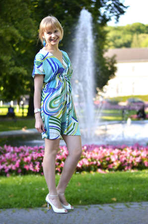 A beautiful young girl is posing in front of the fountain in the park. Stock Photo