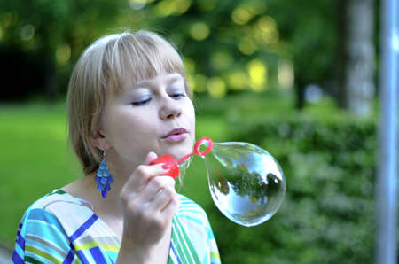 A beautiful young girl is making a big soap bubble and is proud of it.