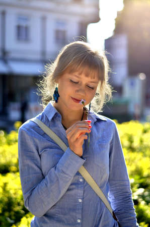 A beautiful young girl is smelling a flower and is dreaming about something.