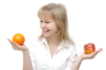 A beautiful young girl like the orange more than an apple. She hast made her decision. photo