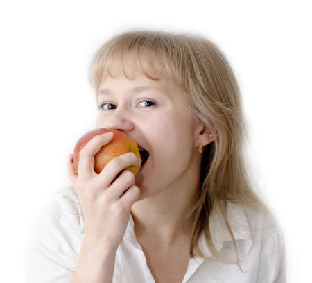 A beautiful young girl is eating an apple and enjoying it. Stock Photo