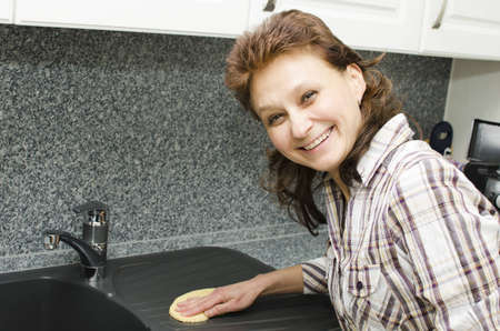 A woman is cleaning the kitchen and enjoys it. Stock Photo