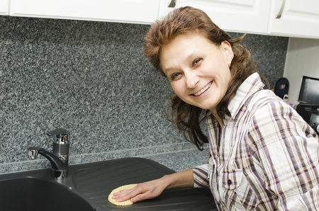 A woman is cleaning the kitchen and enjoys it. photo