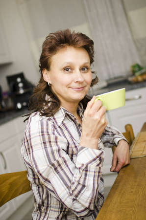 A woman is drinking coffee in the kitchen.