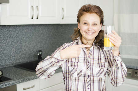 A woman with a glass of orange juice in the kitchen.