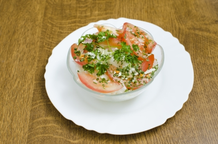 Salad in a transparent cup placed on a plate. Stock Photo