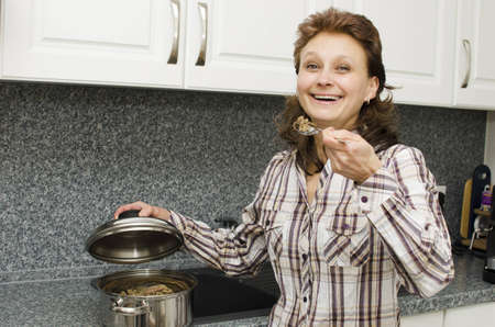 A woman tastes food in the kitchen.