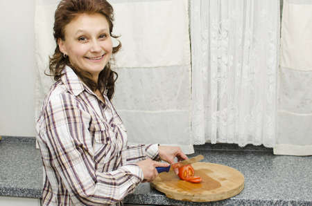 A woman is cutting a tomato in the kitchen.