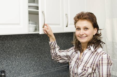 A woman opens a cupboard in the kitchen.