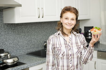 A woman presents a cup of salad in the kitchen.