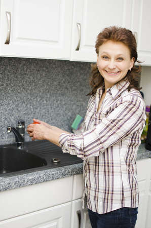 A woman is washing a tomato and enjoys it. Stock Photo