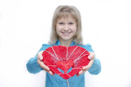 A young woman is holding a heart in her arms   Stock Photo