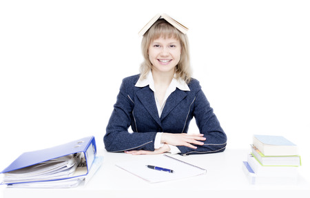 A young woman is sitting at the desk and is studying