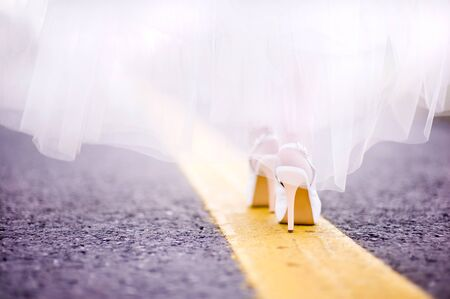 the bride goes along the yellow line along the road Stockfoto