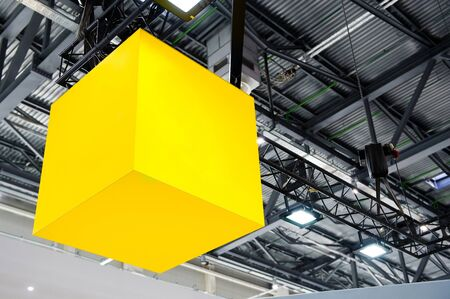 yellow glowing cube suspended under the roof of the hangar Imagens - 129351950
