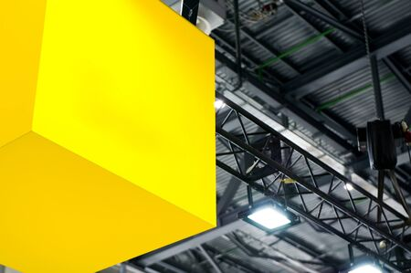 Part of a large luminous yellow cube hanging under the ceiling of a gray defocused hangar occupies about half the area of the image. Imagens