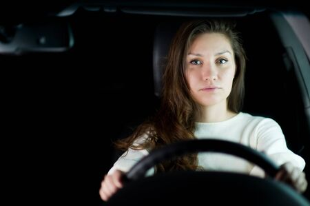 a young girl with her hair holding the steering wheel in a car and looking thoughtfully at the camera. Close-up portrait