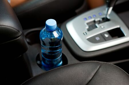 a bottle of drinking water stands in the front cup holder of a vehicle