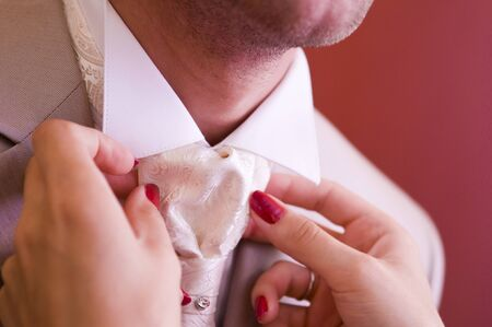 die Braut richtet die Krawatte zum Bräutigam, Nahaufnahme