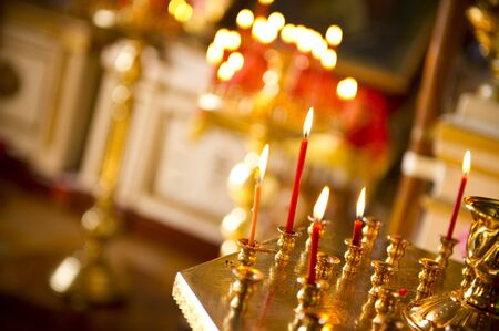 a red candle burns in the church against the background of other candles and the decoration of the church in defocus
