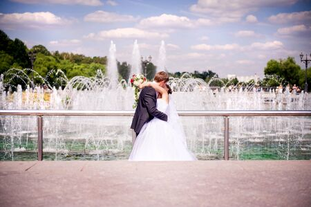 the groom passionately kisses the bride on the background of the fountain behind the chrome railing. faces are turned to each other and the viewer does not see them