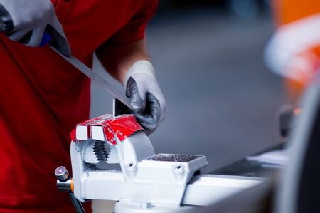 close-up of a worker in a red t-shirt processing a metal workpiece clamped in a vice