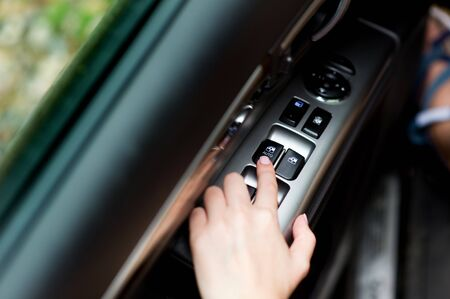hand using electronic power windows in a car Archivio Fotografico