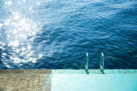 descent into the sea from a concrete slab with a chrome staircase partially painted blue