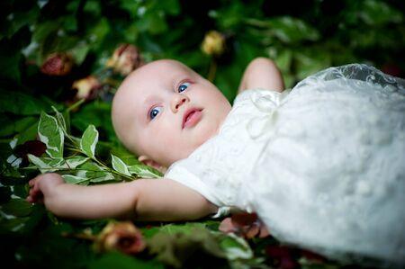 little girl in a white dress lies on green leaves Stok Fotoğraf
