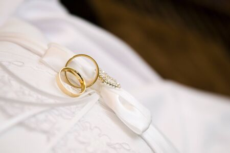 two wedding rings on a white cloth Standard-Bild - 129351914
