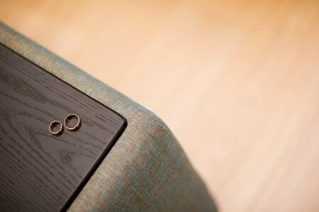 wedding rings on the armrest of the sofa copy space Standard-Bild - 129351918