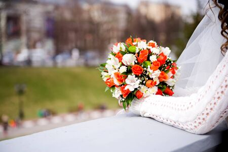 bride holds a wedding bouquet, leaning on a fence Stock Photo