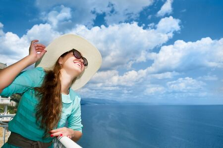 young smiling girl in a light hat, sunglasses on a background of the Black Sea and clouds