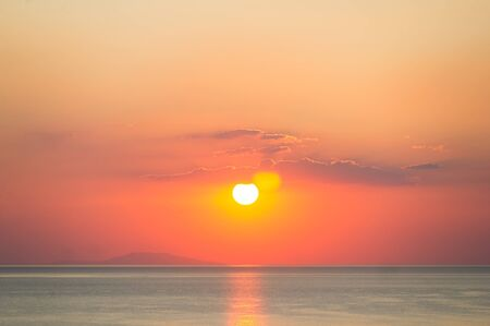 Sunrise over the ocean. Beautiful seascape. Orange sky reflecting on water at dawn. Spiritual new day dawning natural world background image. Фото со стока