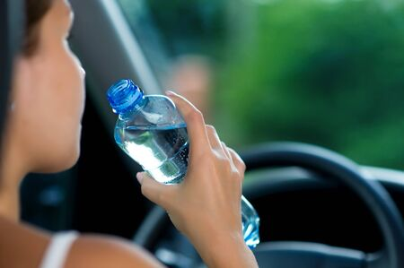 young woman drives a car and is going to drink water from a bottle