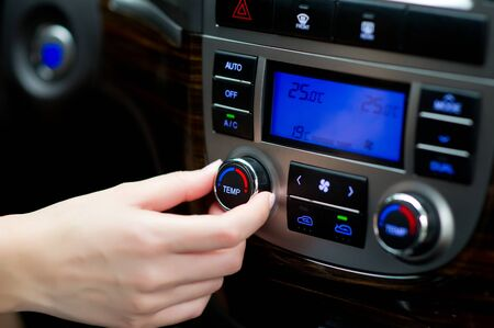 womans hand adjusts climate control in the car Stockfoto