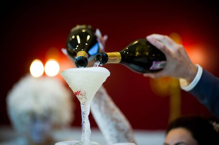 the hands of the bride and groom pour champagne on a slide from the glasses so that it spills over all the glasses