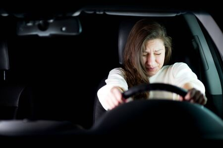 the girl clings tightly to the steering wheel in the car at night and looks frightened in front of herself, trying to avoid a road collision