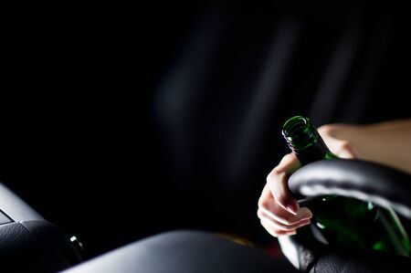 spilled bottle of alcohol, driver's hand and steering wheel Foto de archivo