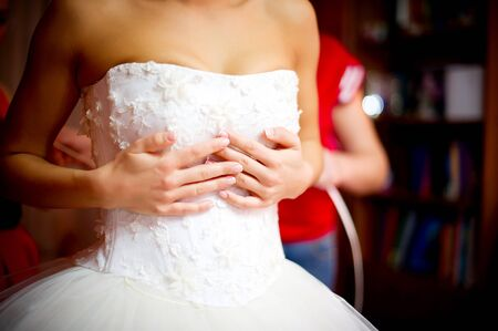 bride holds dress on herself while bridesmaids lace her corset. no face