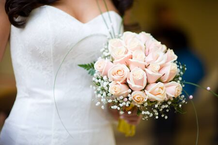 bride holds her bouquet in her arms, close-up, no face