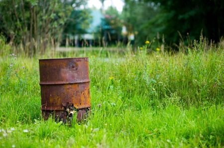 old rusty barrel with holes stands in bright grass against a background of greenery in defocus